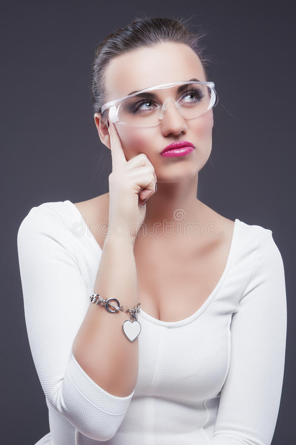 Portrait de plan rapproché de penser la femme caucasienne de brune en verres contre le gris photographie stock