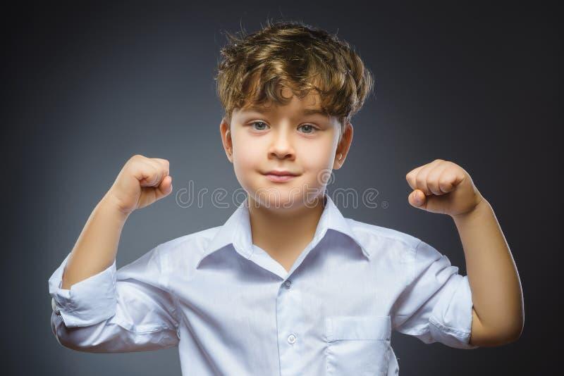 Portrait de plan rapproché de petit enfant drôle représentation de ses muscles de biceps de main L'enfant sérieux fort montrant s images libres de droits
