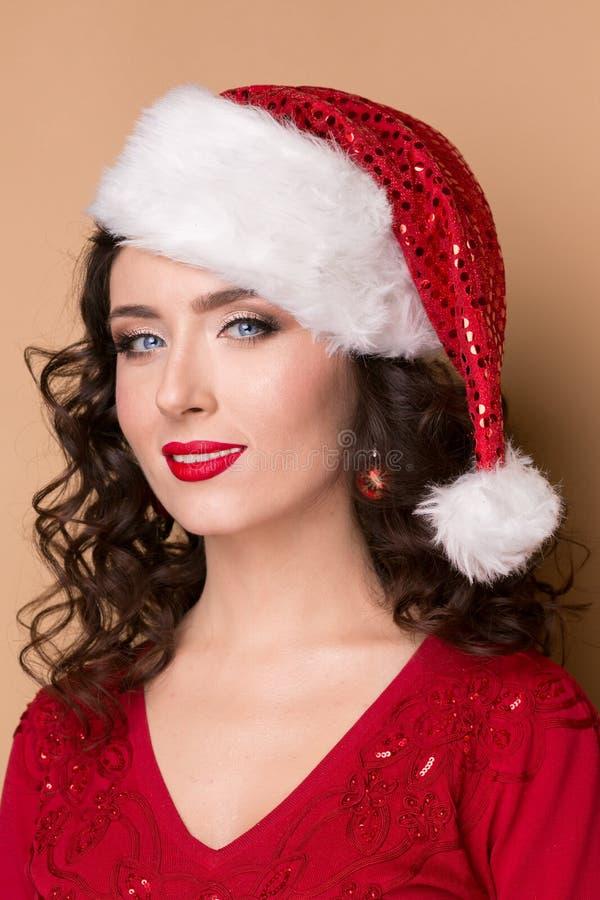 Portrait de plan rapproché de studio d'une belle fille dans le chapeau de Santa Claus, photographie stock libre de droits