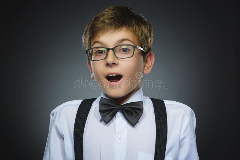 Portrait de plan rapproché de surprise allante de garçon heureux d'isolement sur le fond gris photos libres de droits