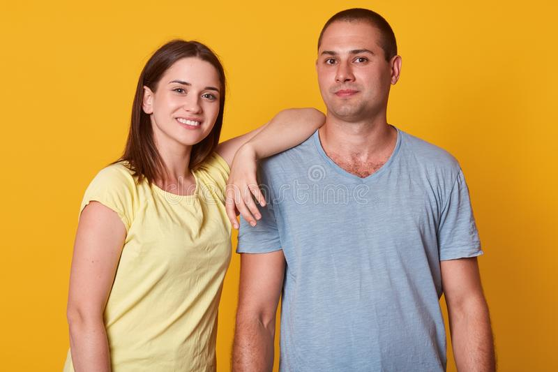 Portrait de plan rapproché des couples paisibles heureux, se tenant au-dessus du fond jaune dans le studio, souriant sincèrement, photos stock