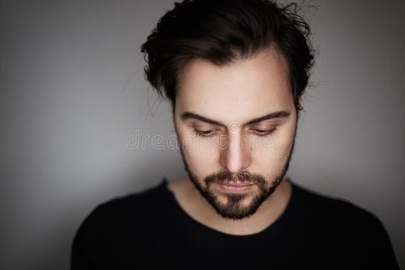 Portrait de plan rapproché du jeune homme beau de mode dans le T-shirt portant en équilibre tout en se tenant sur le fond gris vi photos libres de droits