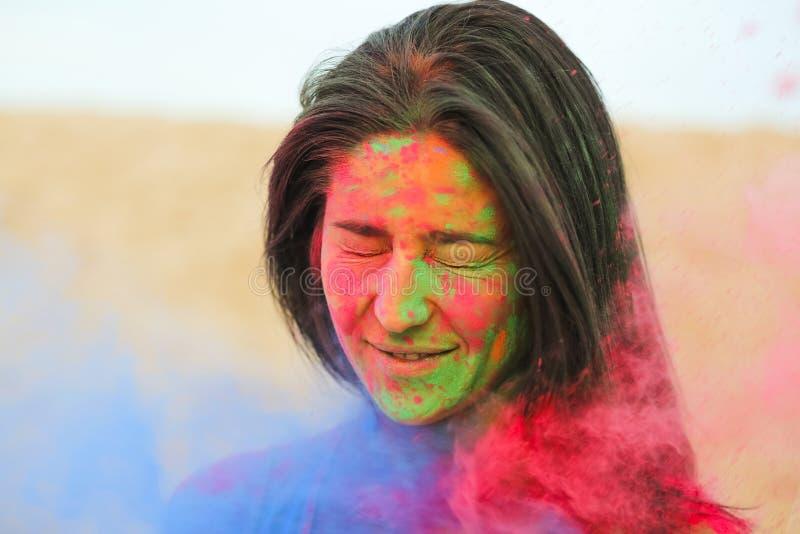 Portrait de plan rapproché du modèle magnifique de brune couvert de peinture colorée de Holi, posant au désert images stock