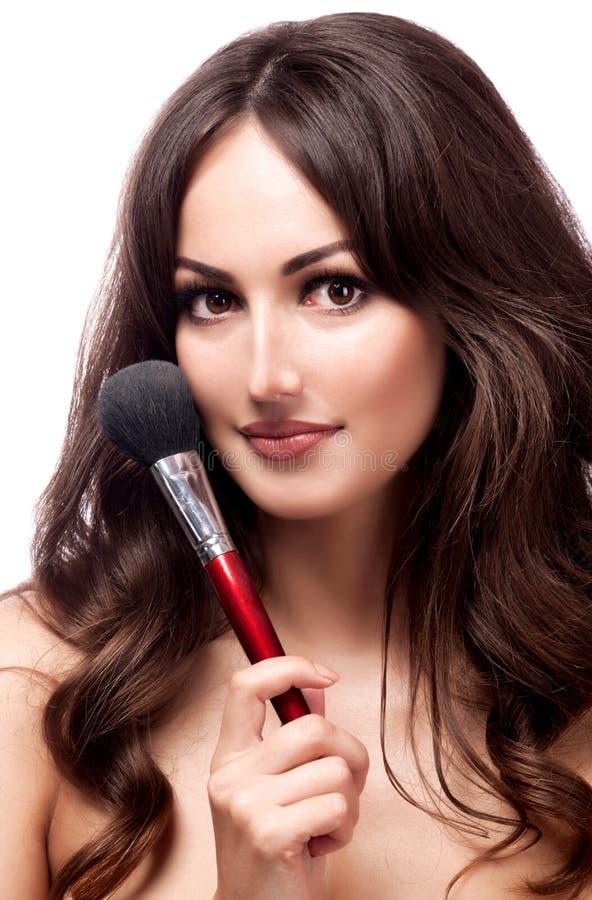 Portrait de plan rapproché de jolie femme avec la brosse cosmétique, dos blanc image stock