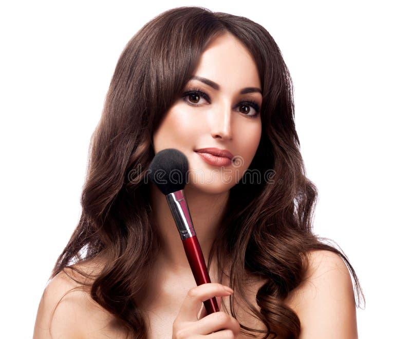 Portrait de plan rapproché de jolie femme avec la brosse cosmétique, dos blanc photos stock