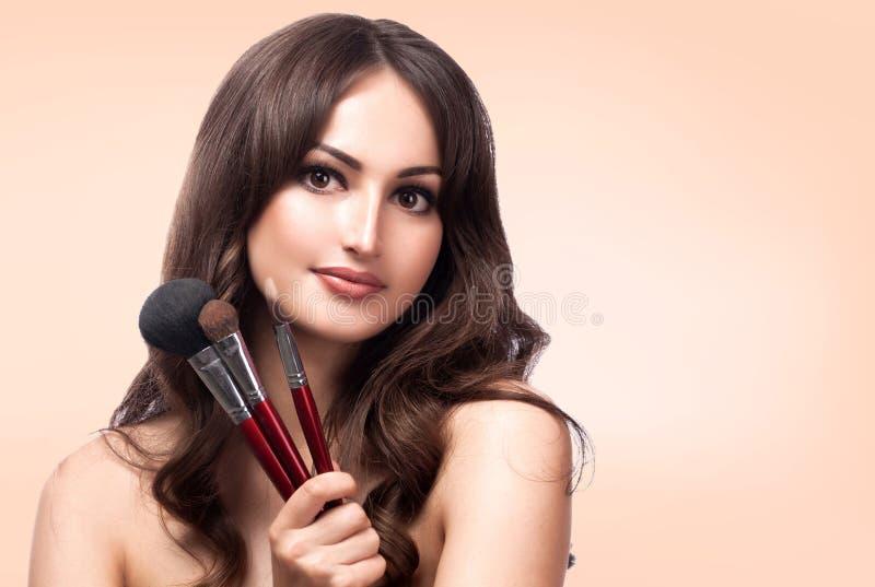 Portrait de plan rapproché de jolie femme avec les brosses cosmétiques photographie stock