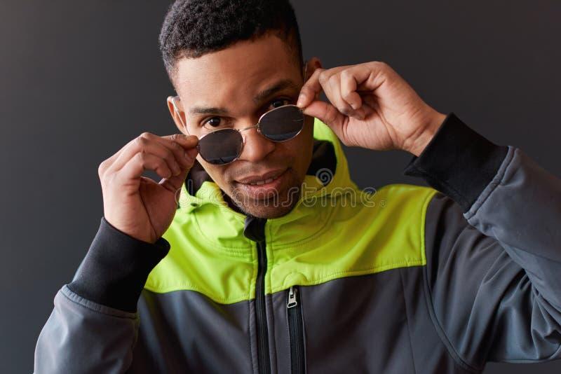 Portrait de plan rapproché de l'homme élégant d'Afro-américain regardant par la pose pour des lunettes de soleil de miroir, posan photo libre de droits