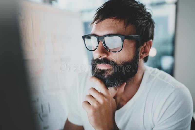 Portrait de plan rapproché de l'homme barbu bel travaillant au grenier moderne de bureau horizontal Fond brouillé cultivé image stock