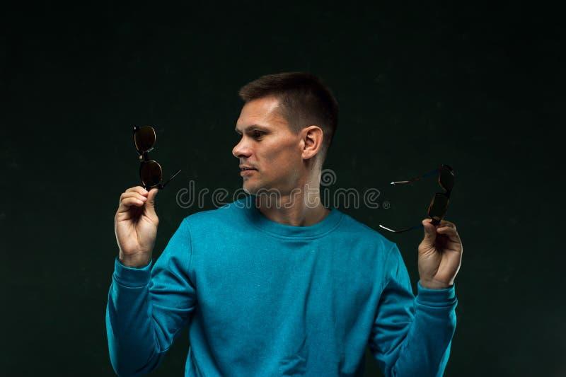 Portrait de plan rapproché de l'homme tenant les lunettes élégantes images stock
