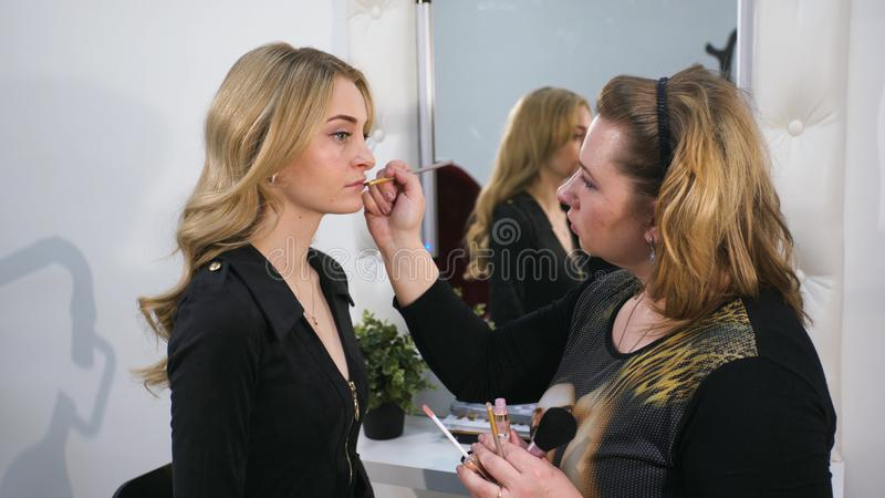Portrait de plan rapproché de la belle femme blonde faisant le maquillage sur ses lèvres photos libres de droits