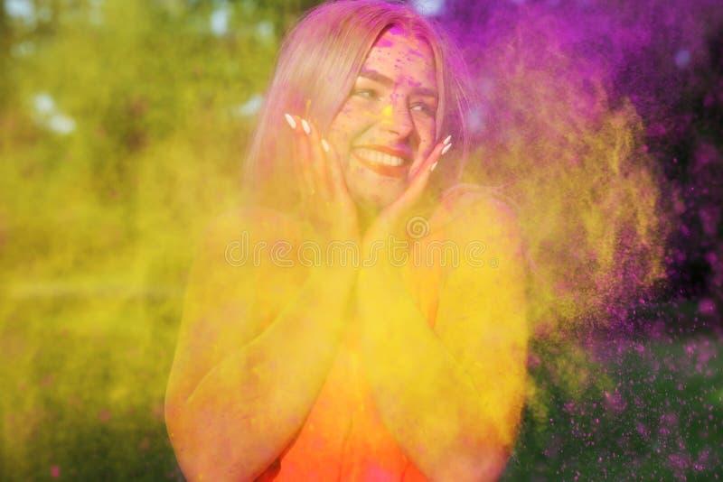 Portrait de plan rapproché de la gentille femme blonde ayant l'amusement dans un nuage de peinture sèche jaune et pourpre de Holi images stock