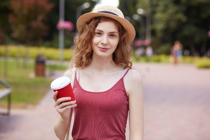 Portrait de plan rapproché de la jeune femelle d'une chevelure bouclée sincère regardant directement la caméra, sourire doux, app photo stock