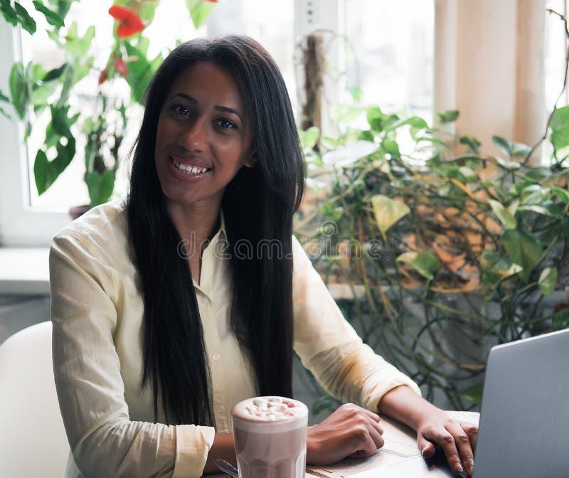 Portrait de plan rapproché de la jeune femme africaine détendant en café avec l'ordinateur portable et faisant l'appel téléphoniq image libre de droits