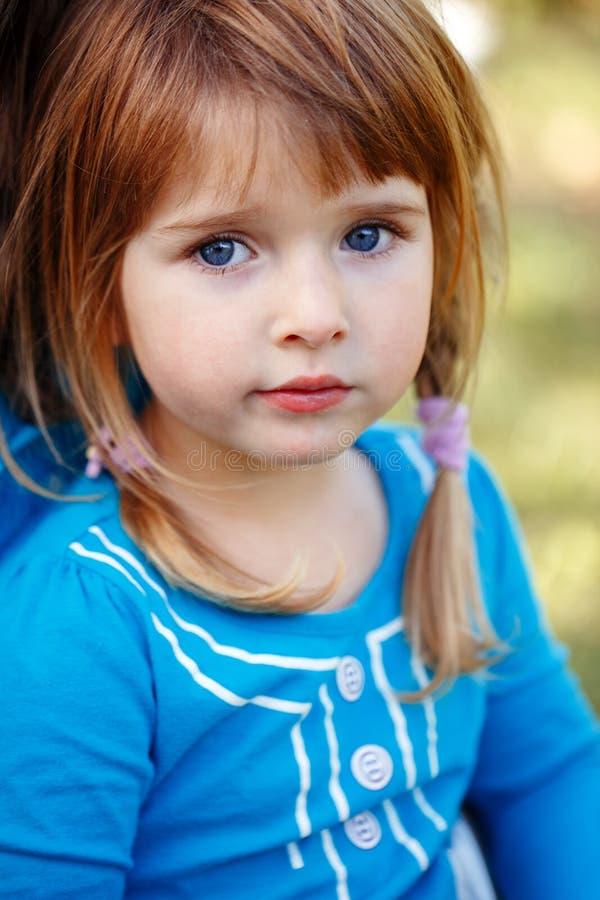 Portrait de plan rapproché de petit enfant caucasien roux adorable mignon de fille avec des yeux bleus photographie stock