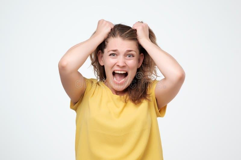 Portrait de plan rapproché soumis à une contrainte, femme choquée frustrante tirant des cheveux hurlant le fond gris d'isolement  images libres de droits