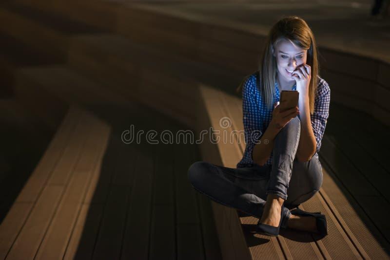 Portrait de plan rapproché souriant ou riant la jeune femme d'indépendant regardant le téléphone voyant de bonnes actualités ou p photographie stock