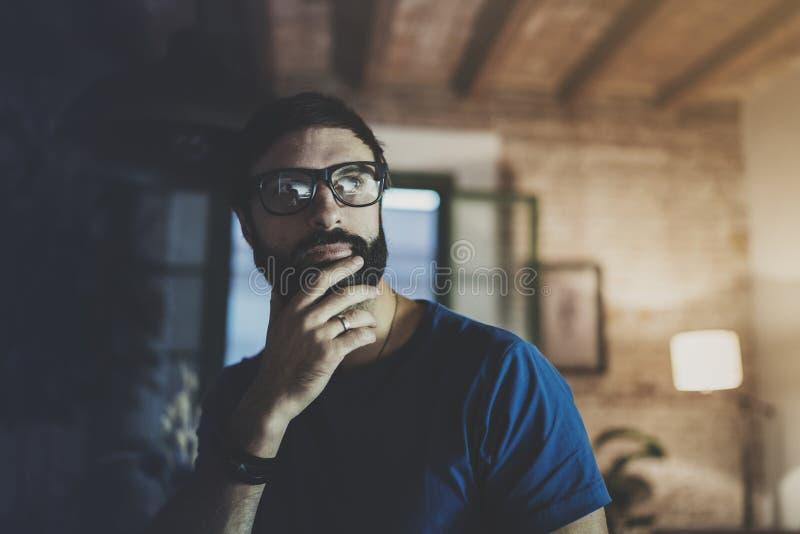 Portrait de plan rapproché de temps de repos barbu beau de dépense d'homme à la maison moderne à la soirée horizontal Fond brouil images libres de droits