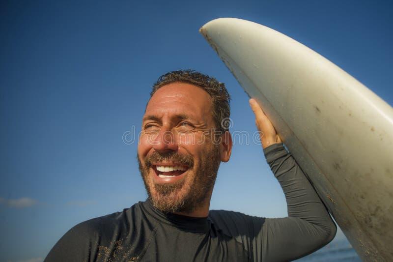 Portrait de plan rapproch? de plage de mode de vie d'homme beau et attirant de surfer dans le maillot de bain du n?opr?ne jugeant photo libre de droits