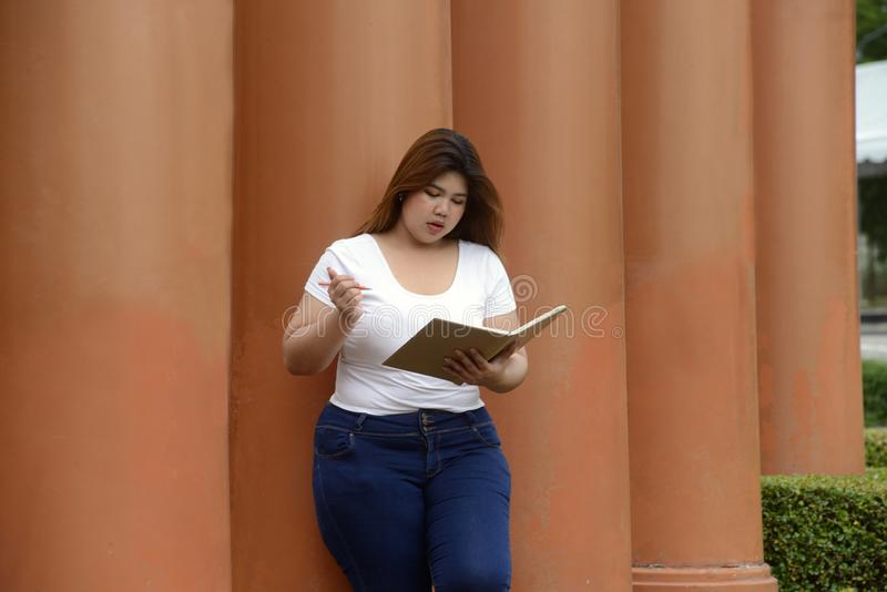 Portrait de pose assez grosse et de la pensée de femme d'Asiatique à un poteau photos libres de droits