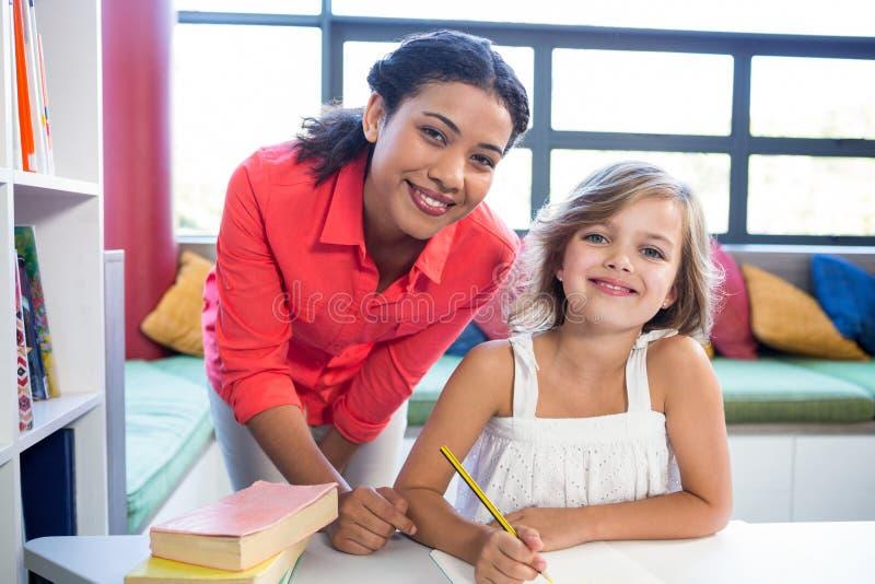 Portrait de professeur avec la fille dans la bibliothèque d'école photos stock