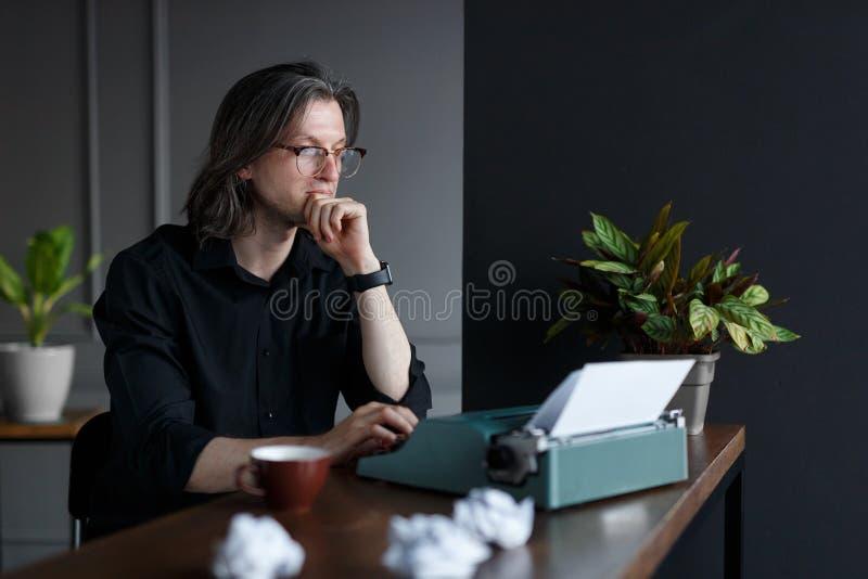 Portrait de profil d'un jeune bussinesman, posé à la table, près de la machine à écrire Tir dans le studio, au-dessus du fond gri photo libre de droits