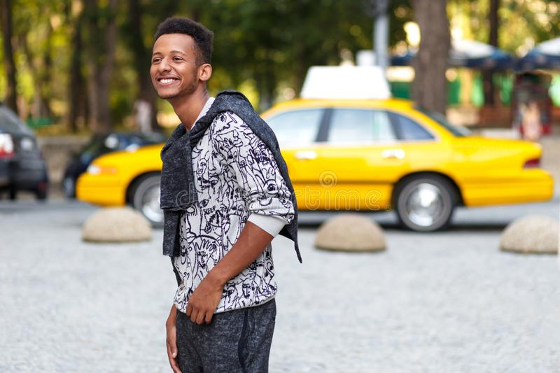 Portrait de profil d'un jeune homme drôle dans des vêtements sport, marchant dans le temps de jour, sur le fond brouillé de rue images libres de droits