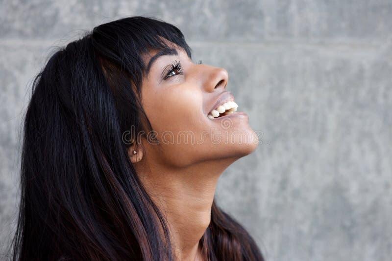 Portrait de profil de la jeune femme indienne riant et recherchant image libre de droits
