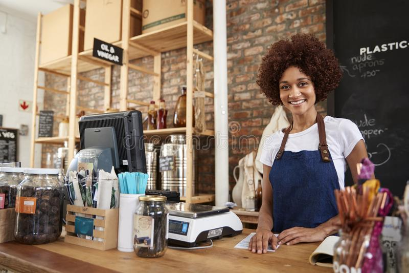 Portrait de propriétaire féminin d'épicerie libre en plastique viable derrière le bureau de ventes photographie stock libre de droits