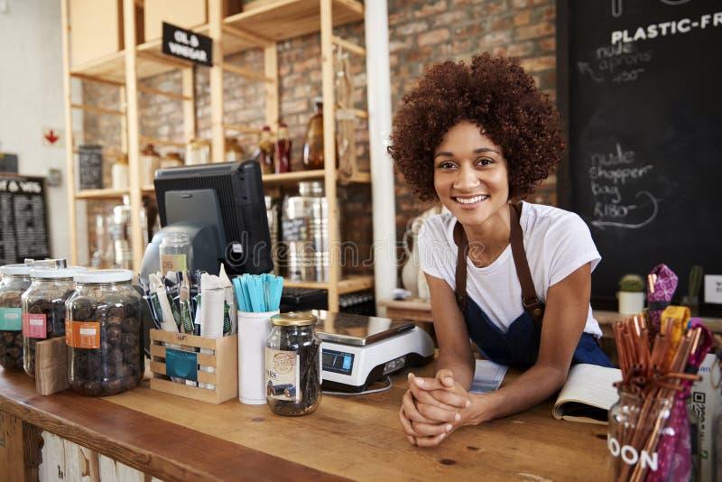Portrait de propriétaire féminin d'épicerie libre en plastique viable derrière le bureau de ventes photos stock