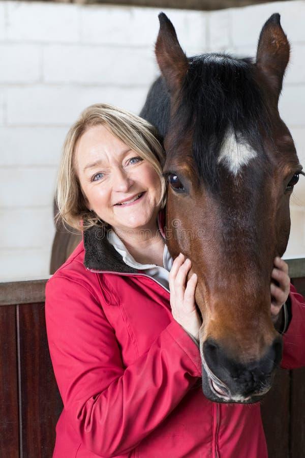Portrait de propriétaire féminin mûr dans l'écurie avec le cheval photographie stock libre de droits