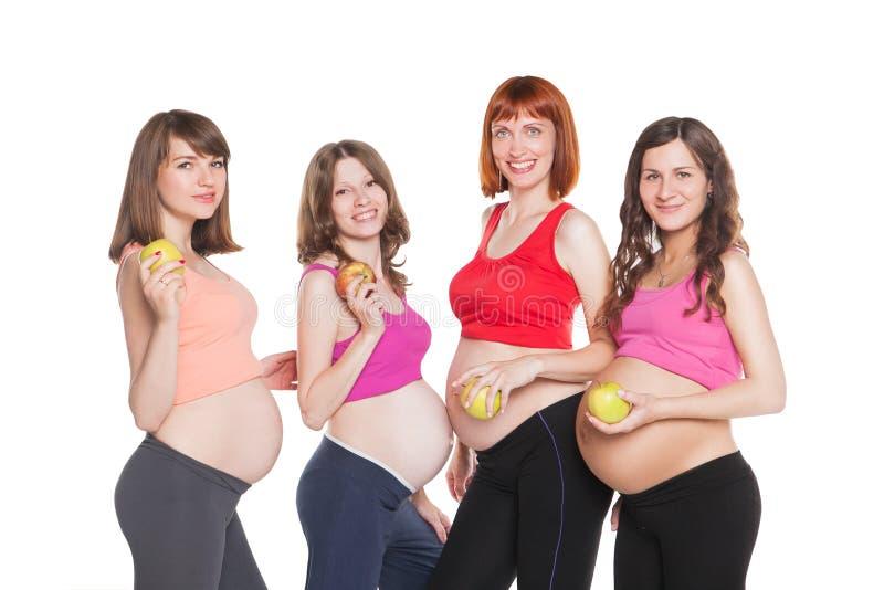 Portrait de quatre femmes enceintes heureuses avec des fruits image stock