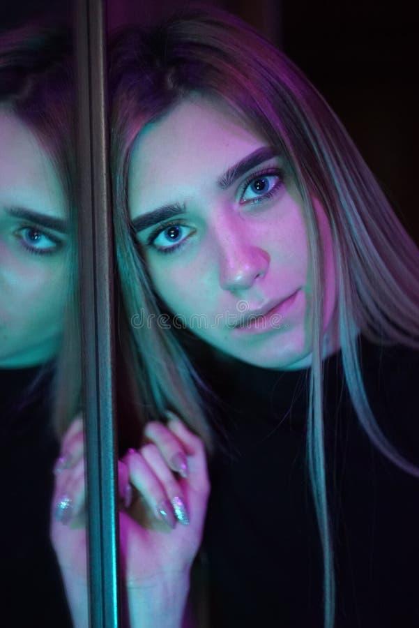 Portrait de réflexion d'individu de stupéfier la jeune fille dans la fenêtre reflétée Jolie personne étrange peu commune de femme images stock
