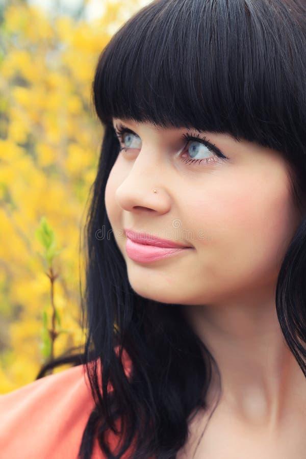 Portrait de ressort d'une belle brune dans fleurs jaunes images libres de droits