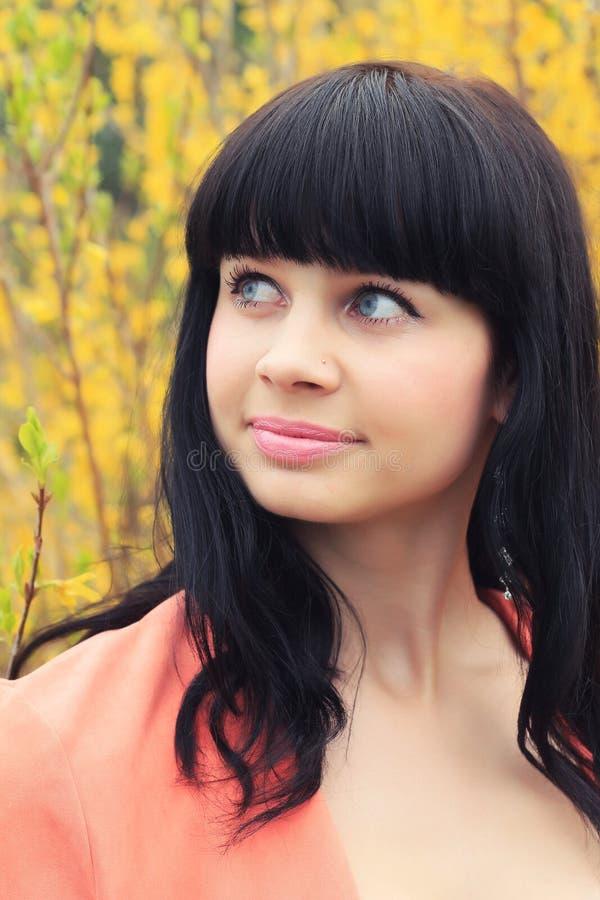 Portrait de ressort d'une belle brune dans fleurs jaunes photographie stock libre de droits