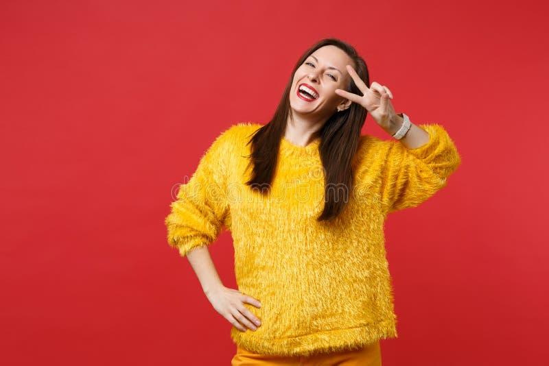 Portrait de rire la jeune femme drôle dans le signe jaune de victoire d'apparence de chandail de fourrure d'isolement sur le fond image libre de droits