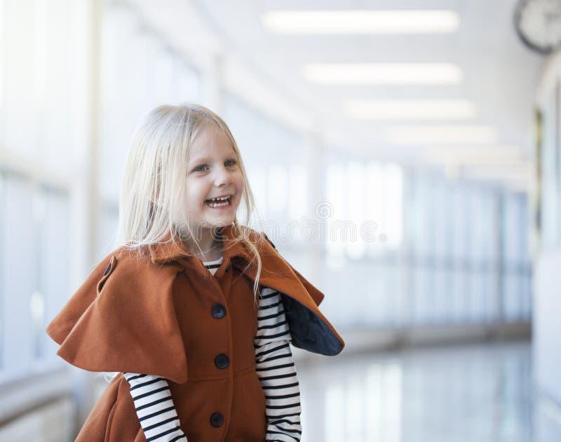 Portrait de rire la petite fille portant le manteau orange à la mode photo stock