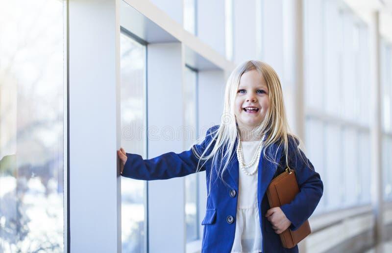 Portrait de rire la petite fille portant la veste bleue et les perles image stock