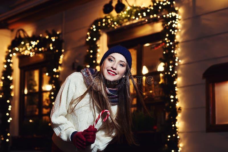 Portrait de rue de nuit de belle jeune femme de sourire avec la canne de sucrerie de Noël Looking modèle à l'appareil-photo Port  images stock