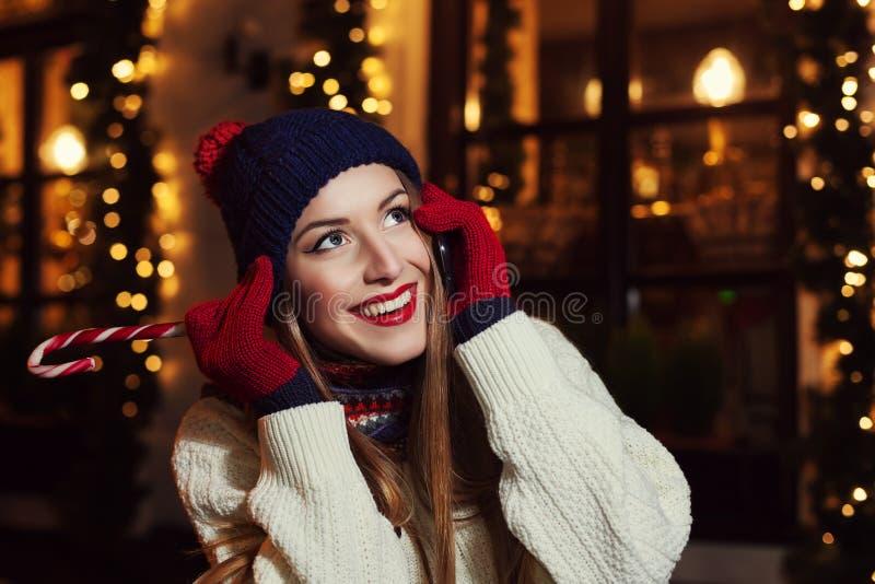 Portrait de rue de nuit de la belle jeune femme de sourire parlant du téléphone portable et recherchant Classique de port de Mada photos stock