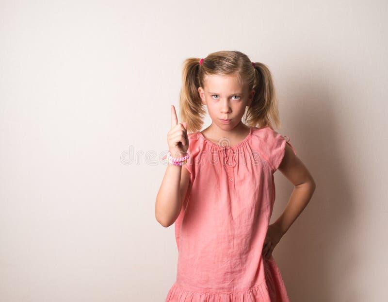 Portrait de sérieux, fronçant les sourcils, fille fâchée et grincheuse dirigeant le finge photo stock