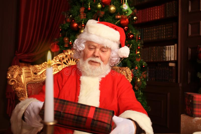 Portrait de Santa Claus heureuse se reposant à sa pièce à la maison près de l'arbre de Noël avec le boîte-cadeau photographie stock libre de droits