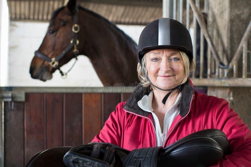 Portrait de selle femelle mûre de participation de propriétaire dans l'écurie avec Ho photographie stock