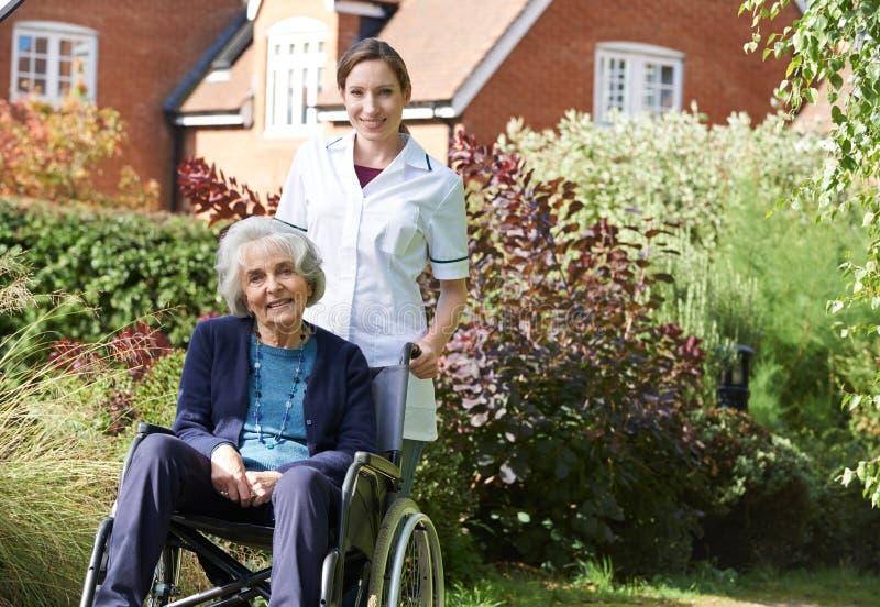 Portrait de soignant poussant la femme supérieure dans le fauteuil roulant images libres de droits