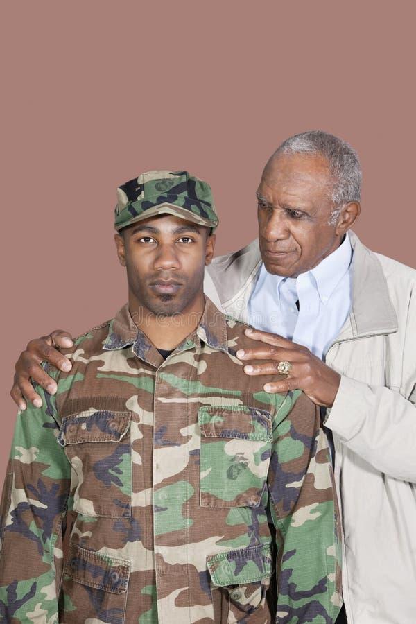 Portrait de soldat des USA Marine Corps de mâle d'Afro-américain avec le père au-dessus du fond brun photographie stock
