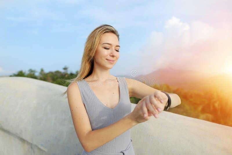 Portrait de soleil de la jeune fille caucasienne employant le smartwatch, montagnes à l'arrière-plan, Bali photos libres de droits
