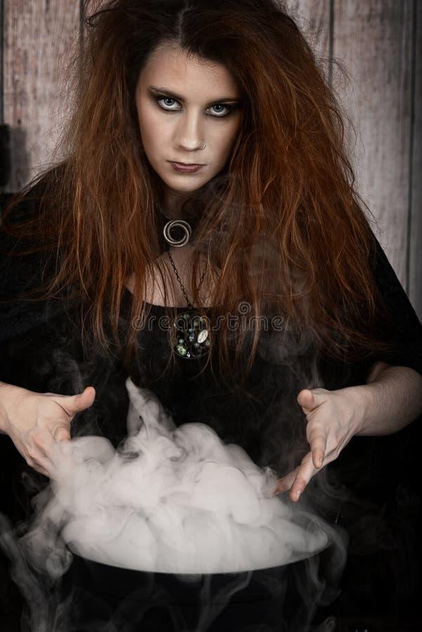 Portrait de sorcière avec le chaudron de tabagisme magique image stock