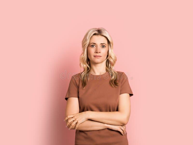 Portrait de sourire attrayant adulte de femme blonde beau, fille caucasienne sur le fond rose photographie stock