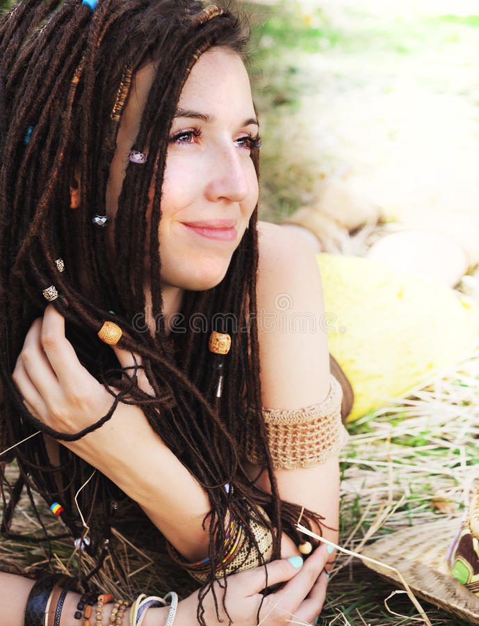 Portrait de sourire calme de fille avec des dreadlocks, se reposant sur l'herbe sèche en parc photos stock