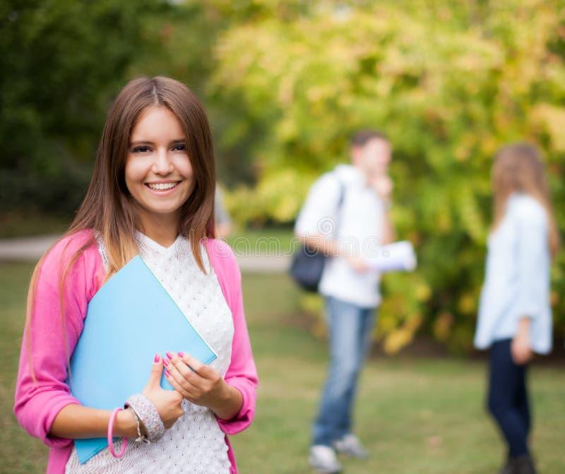 Portrait de sourire d'étudiant tenant un livre photographie stock