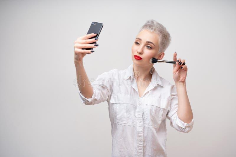 Portrait de studio de belle fille ? la mode avec les cheveux courts et composer reporter le bras sur la taille et prendre le self photo libre de droits